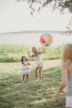 Three people playing catch with a beach ball.