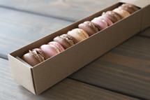 A box of macarons on a wooden table.