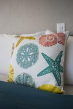 a beach themed throw pillow on a bed