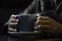 a girl holding a steaming cup of coffee at a Bible study