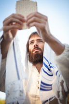 Levitical Priest Bible Character Breaking Bread from the Torah offering Communion representing the bread of life while wearing a prayer shawl