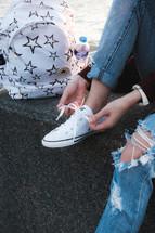 a woman tying her shoe