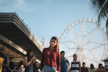 a woman standing in a crowd with a ferris wheel in the background