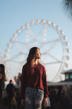 woman with a ferris wheel in the background