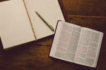 Empty journal with blank pages and a pen on a wooden table with an open Bible.