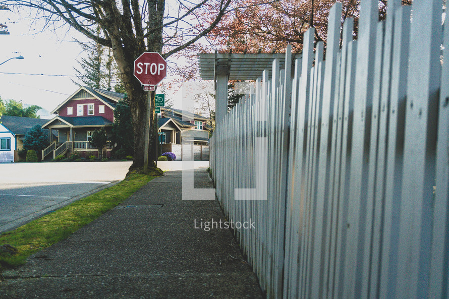 stop sign and white picket fence