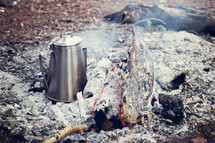 coffee pot in ashes at a campfire site