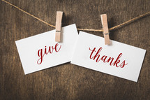 words give thanks on white card stock hanging from a clothespin on a clothesline