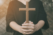 a woman holding a wooden cross