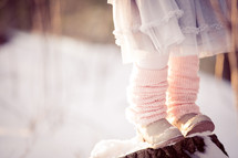 a girl with leg warmers standing in the snow