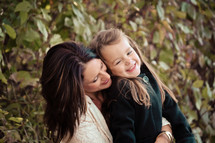 Mother embracing daughter with laughter.