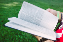 man reading a Bible in the grass
