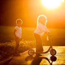 kids with a scooter in warm sunlight