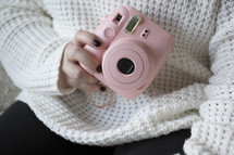 a woman holding a pink camera