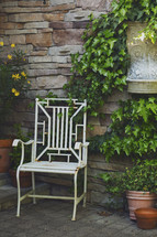 a chair on a patio and ivy growing up the wall