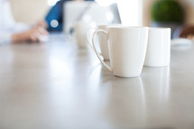 coffee mugs on a conference table