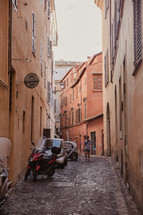 vespas parked on a narrow street in Italy