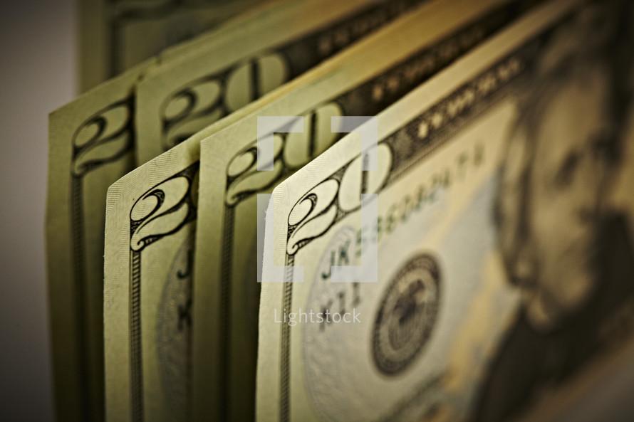A stack of twenty dollar bills standing upright