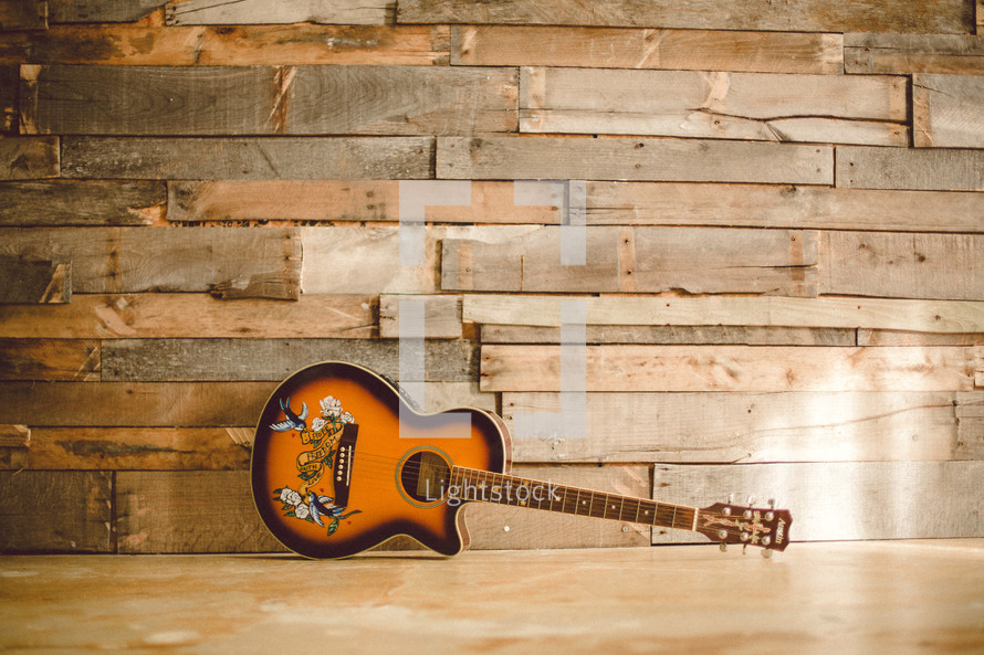 Acoustical guitar on the floor, leaning against the wall.