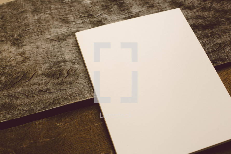 Blank piece of paper on a wooden table.
