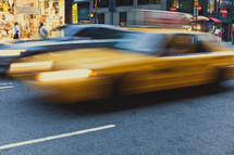 A blurred yellow cab driving by