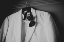A white tuxedo and black bow tie