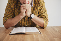 man reading a Bible with his hands folded in prayer