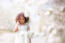 a little girl in a white dress standing in an orchard