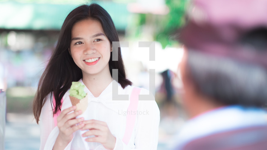 a smiling girl holding an ice cream cone