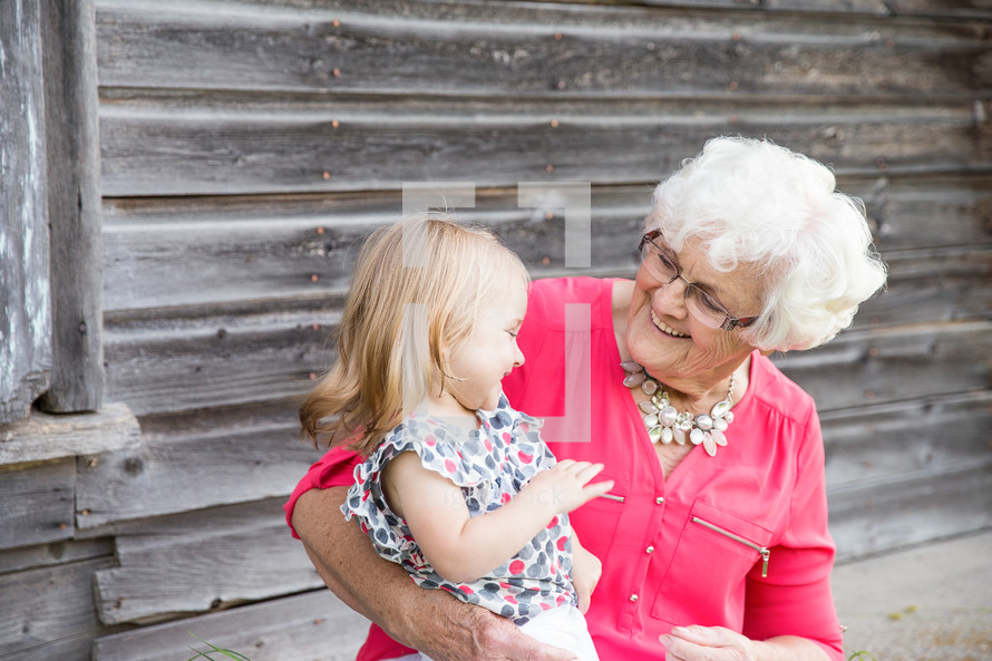 a great-grandmother and granddaughter hugging, smiling
