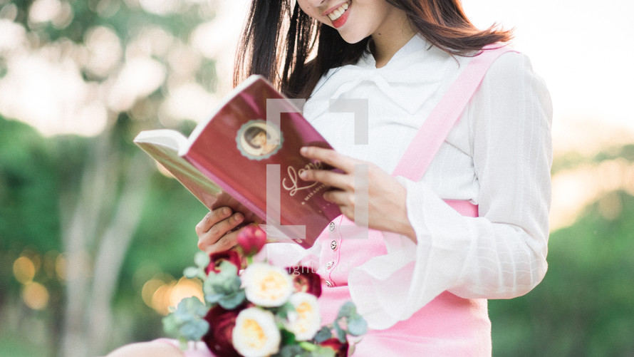 a woman sitting in the grass with a bouquet of flowers in her lap reading a love book