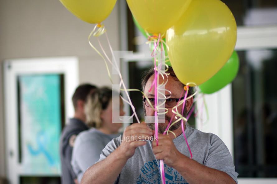 man holding helium balloons