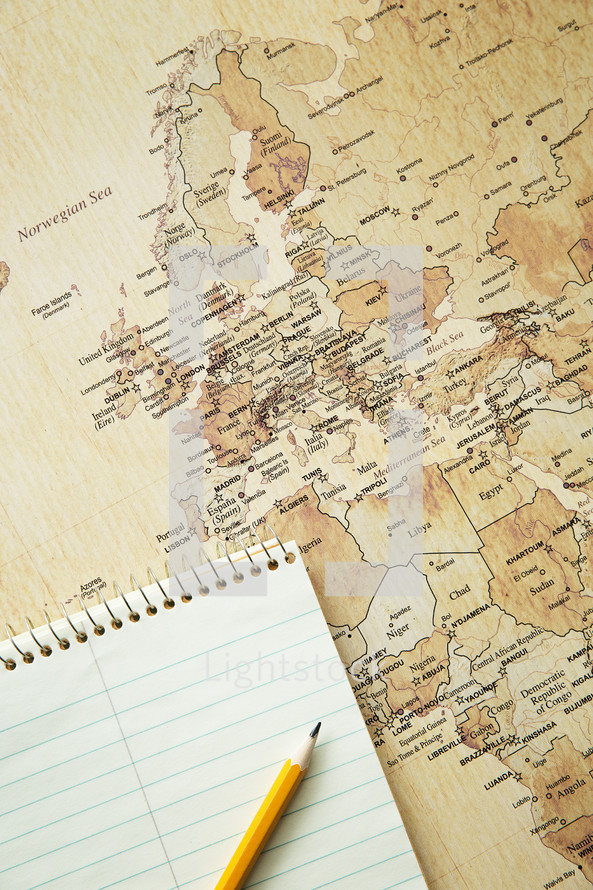 notebook and pencil on a world map
