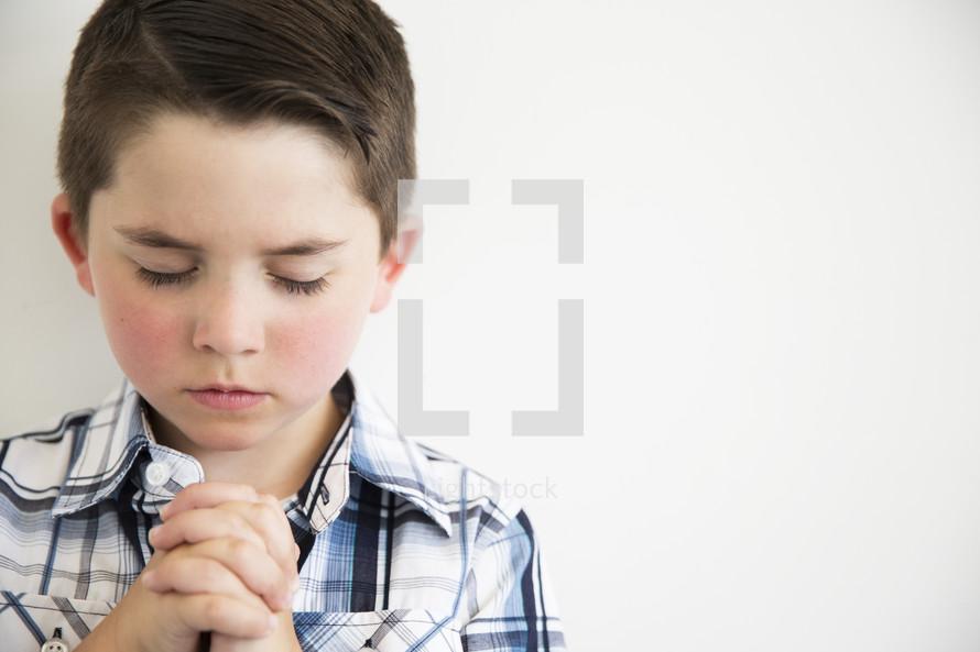 a little boy in prayer.
