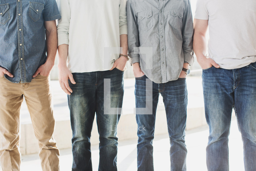 torsos of men standing in a row outside.