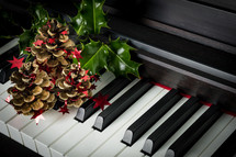 holly and pine cones on a piano