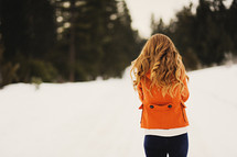 Young woman in an orange coat walking in the snow.
