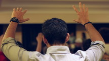 man with hands raised at a worship service
