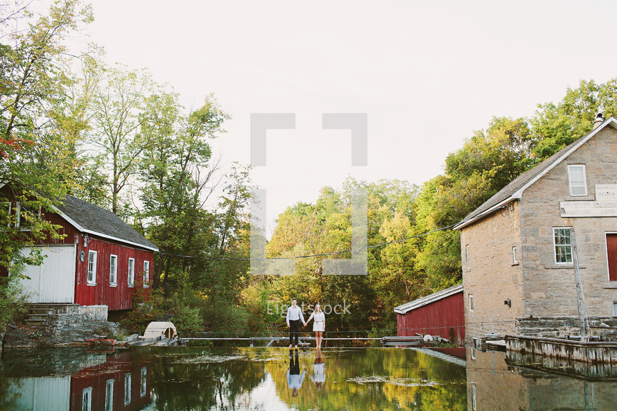 a couple standing together by a mill