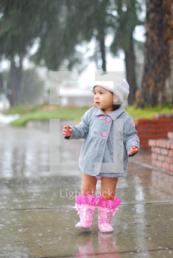 Toddler girl wearing coat, hat and rainboots in rain on wet sidewalk.