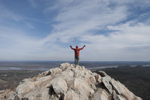 man standing on top of a mountain with his hands raised in worship to God