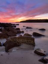 sunrise over rocks along a beach shore