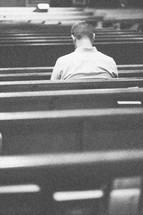 Man praying in a church pew.