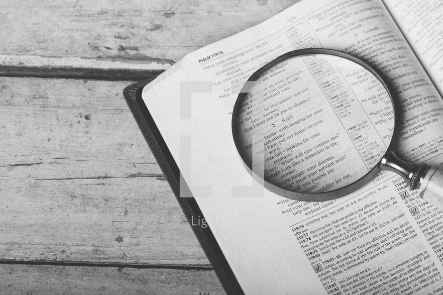 Magnifying glass on page of Bible open to Psalm 119.