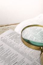 Magnifying glass on top of pages of open Bible.