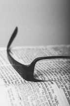 Reading glasses on pages of open Bible.
