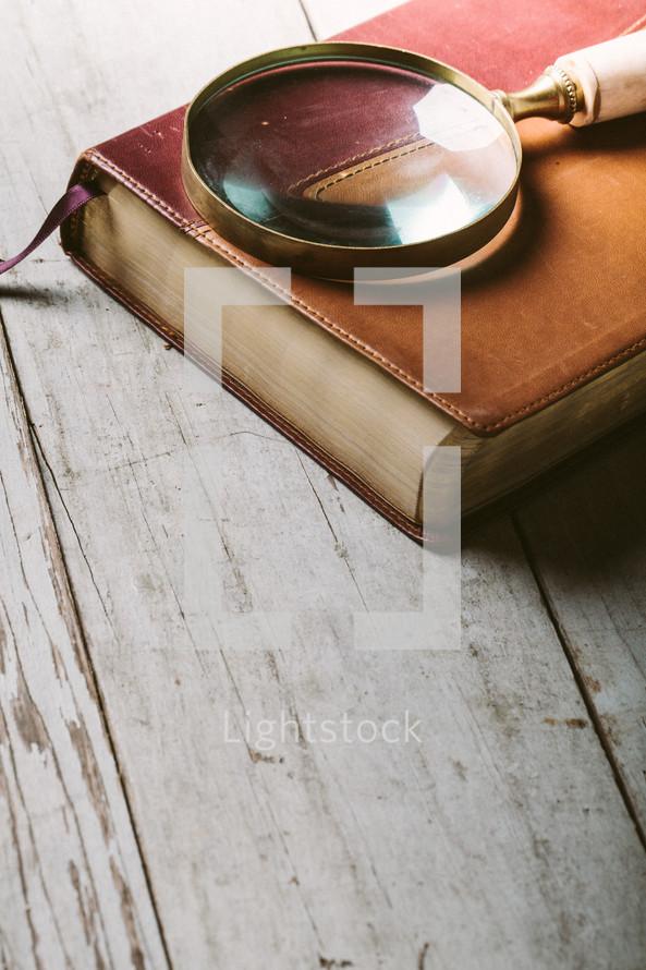 Magnifying glass on top of Bible laying on wooden table.