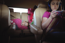 sisters riding in the backseat of a car