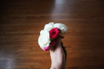 hand holding out a corsage