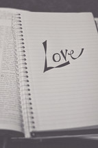love on a notebook on the pages of a Bible